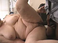 Plump granny sucks black cock and fucks on table